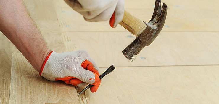 Man Showing How to Nail Hardwood Flooring Using a Nail Setter