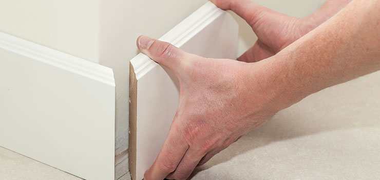 Hands Removing White Baseboards From Wall