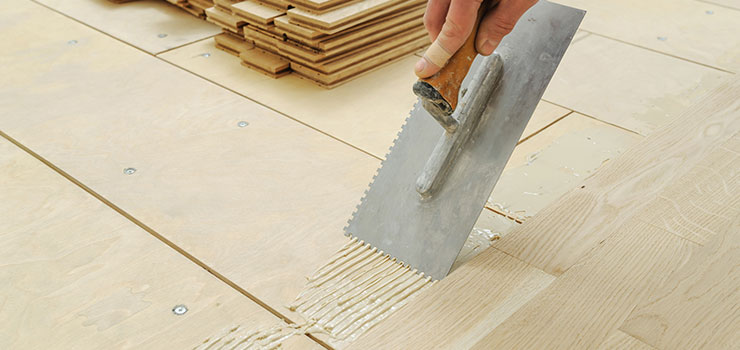 Man Spreading Flooring Adhesive With Trowel to Install Hardwood Flooring