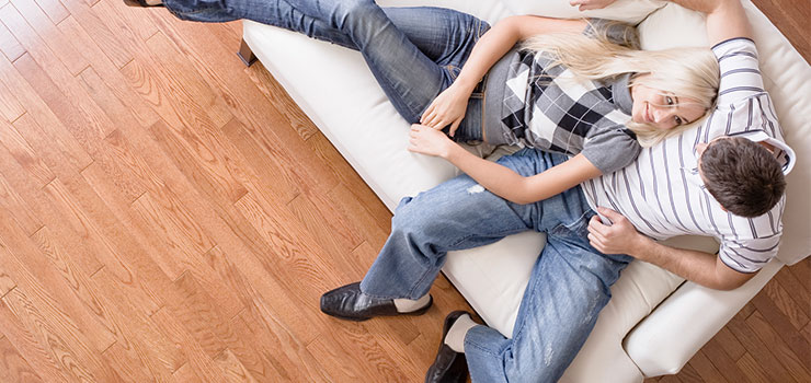 Young Couple Sitting On Couch Admiring New Hardwood Floors